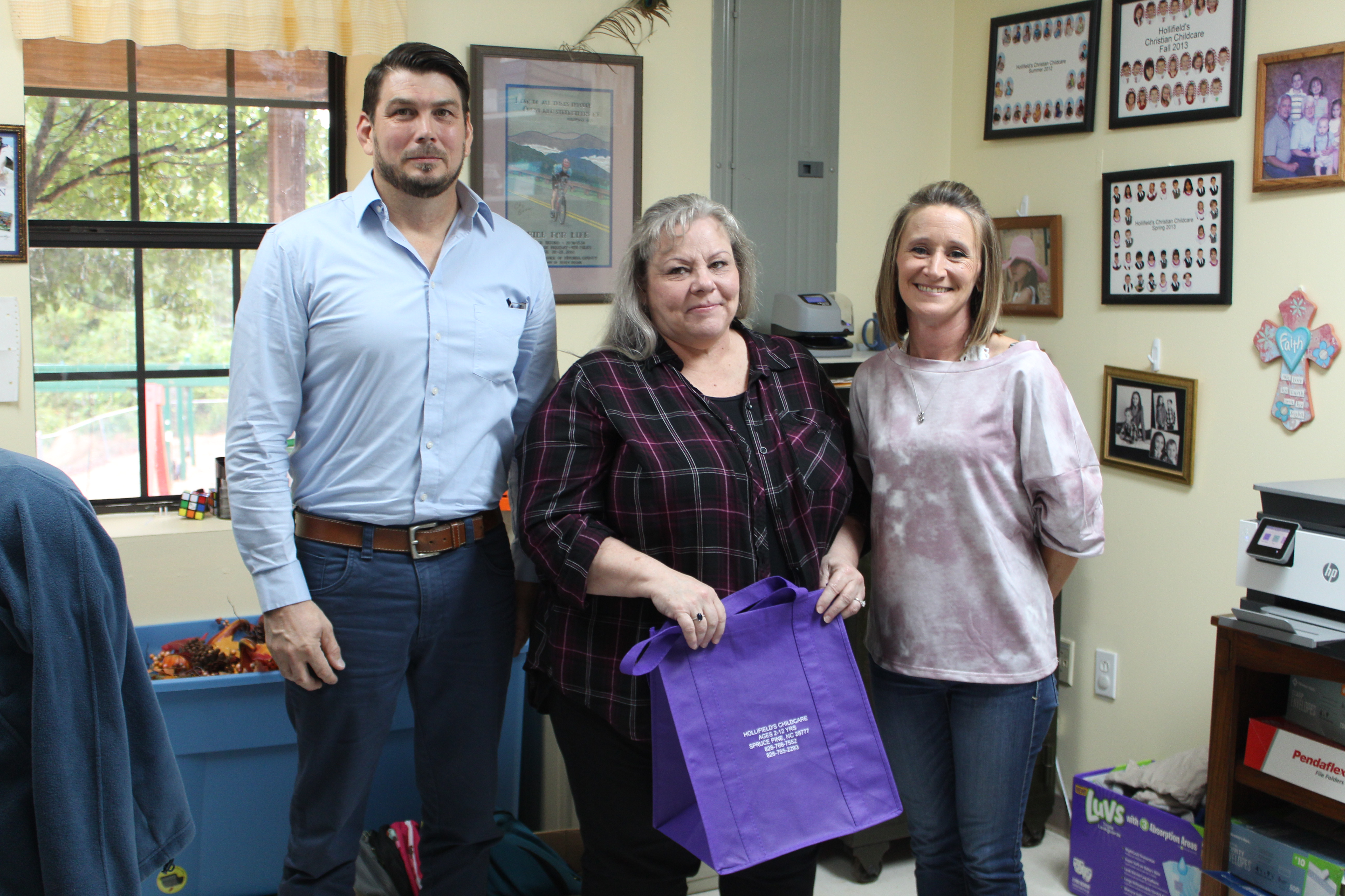 Mitchell County Department of Social Services Program Director Shawn Block, Adoption and Licensing Worker Donna Davis and Hollifield's Christian Child Care Center Director Donna Woody pose for a photo with one of the purple tote bags the children's center donated to DSS. The tote bags will go to children in DSS custody so they don't have to move their belongings in trash bags when they move to a new home. (MNJ photo/Juliana Walker)