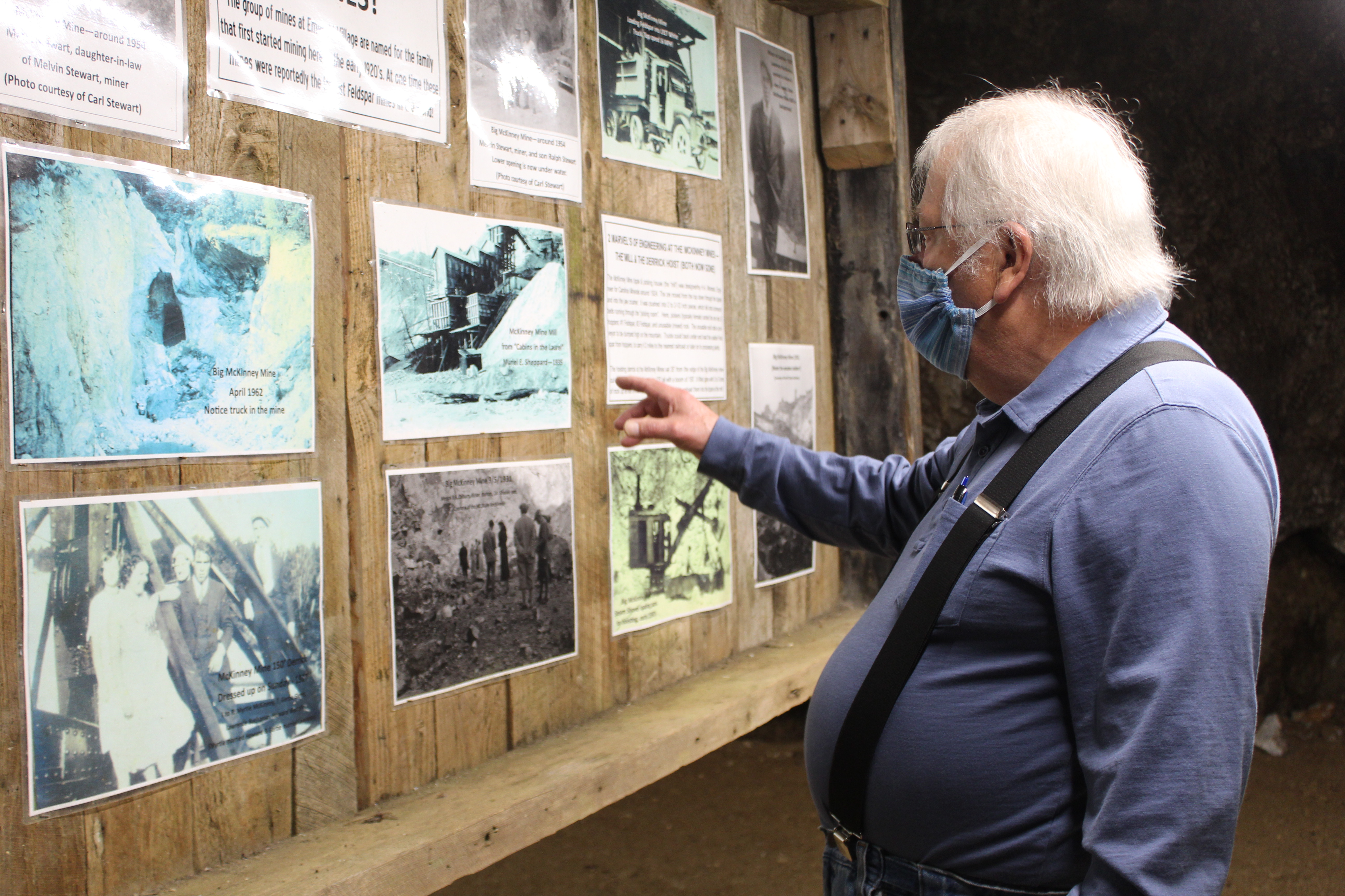Emerald Village Owner Alan Schabilion points to historic photos of old mining operations displayed inside the Bon Ami Mine in Little Switzerland. (MNJ photo/Juliana Walker)