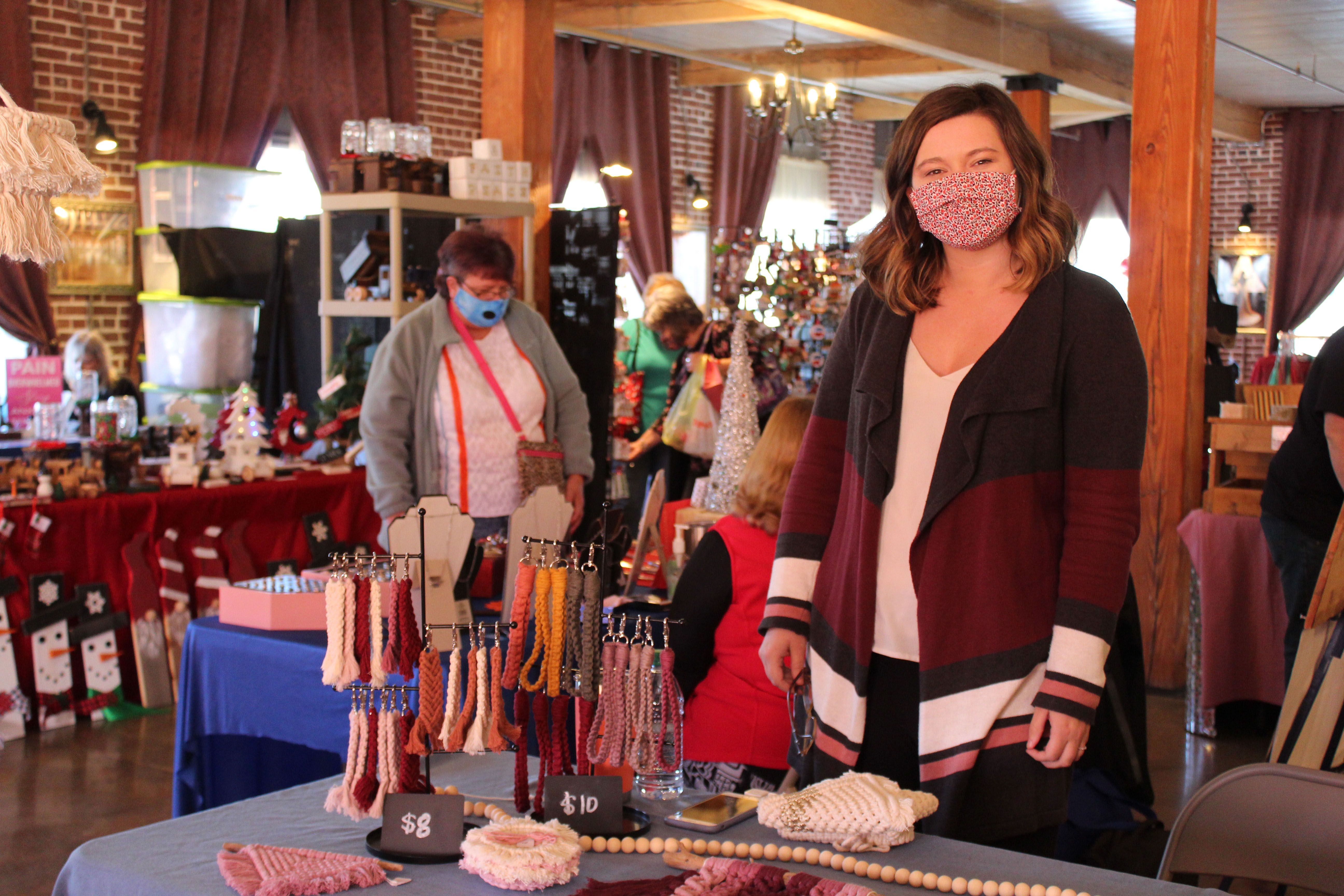 Mitchell County native Brittney King keeps watch over her booth at the Spruce Pine Southern Christmas Show on Saturday, Nov. 28 at the Cross Street Commerce Center. King, who heard about the show from a fellow craftsman, was one of 40 vendors set up at the show. (MNJ photo/Juliana Walker)
