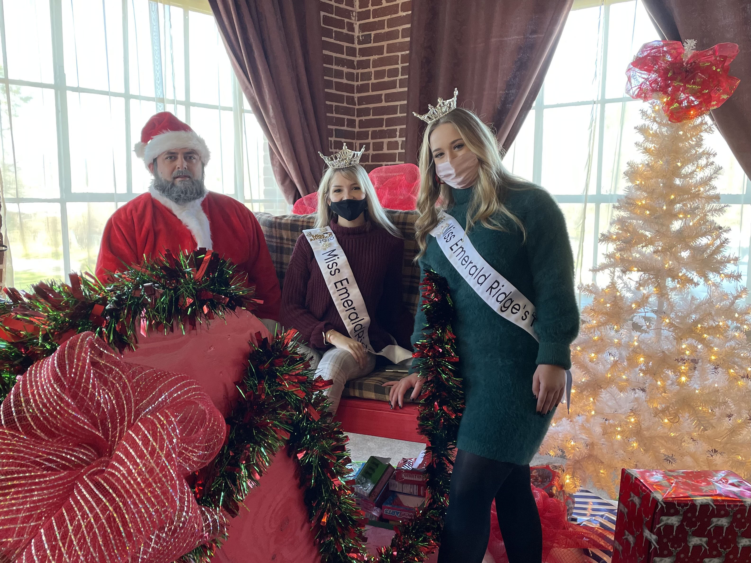 Santa Claus and local beauty pageant queens Miss Emerald Ridge Tessa Rabideau and Miss Emerald Ridge Outstanding Teen McKenna Harvey pose for a group photo on Saturday, Nov. 28 during the Spruce Pine Southern Christmas Show. (MNJ photo/Juliana Walker)