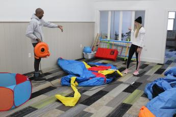 John Williams and his wife, Whitney, arrange inflatable bouncy houses inside their new business, Wren and Wrae's Clubhouse, at 218 Oak Ave. in Spruce Pine.  The clubhouse offers inflatables, toys and other options for children while Whitney, a personal trainer, will use part of the building to host a variety of exercise classes for adults. Wren and Wrae's will also be available to host birthday parties and other events. (Brandon Roberts/MNJ)