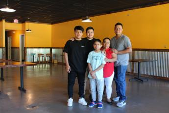Claudia Pile and her three sons, left to right, Johnny, James and Joshua Pile, and husband Victor Hernandez in their new  restaurant space in the Spruce Pine Commons  Shopping Center. They hope to open the new location in two weeks. Photo by Juliana Walker/MNJ.