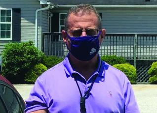 Mitchell County Sheriff Donald Street dons his mask as he prepares to head out on patrol. Street said masks are not a political issue and said he plans to wear one if it helps protect others. He encourages the public to do the same. (Submitted photo)