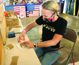 Kendall Chandler, owner and developer of The Quill and Honey, wraps up soap bars to prepare them for sale Friday, July 31 during the Rock Hound Craft and Vintage Market at Cross Street Commerce Center. Chandler came to the show from Forks of Ivy. (MNJ photo/Cory Spiers)