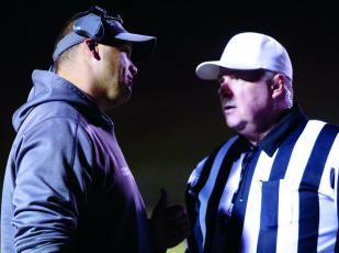 Mitchell High School head varsity football coach Travise Pitman talks things over with an official during a 2019 state playoff game. Pitman and his team will return to play in February. (MNJ file photo)