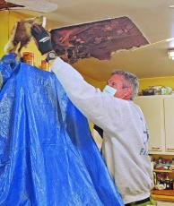 This past fall, volunteers from Spruce Pine United Methodist Church rallied to support a local senior with roof repairs. Volunteers restored the ceiling where water levels had caused damage. Pictured above repairing the ceiling is volunteer Mike Murphy. (Submitted photo)